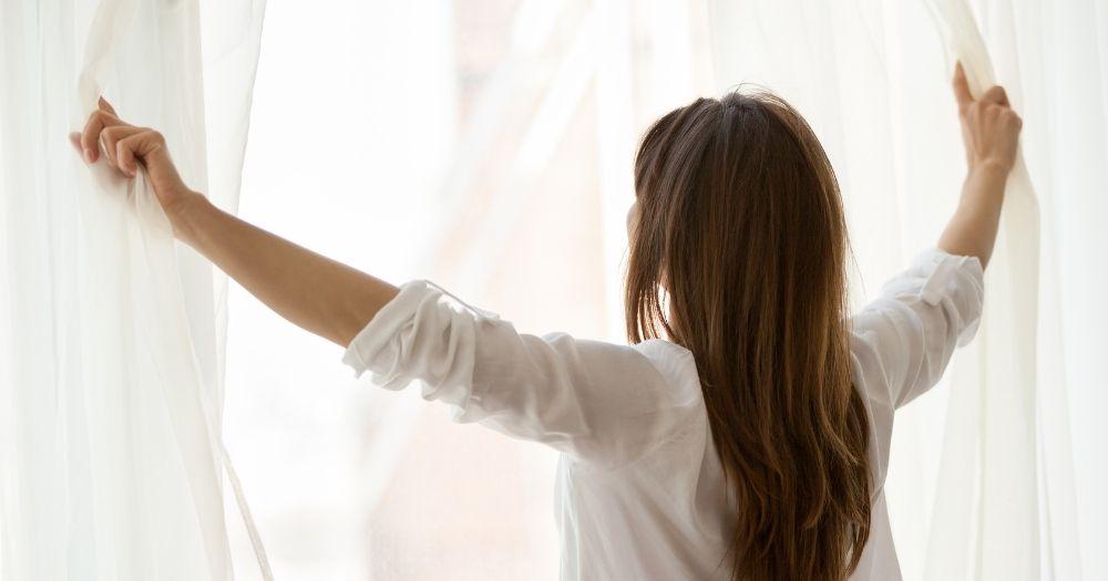 Γυναίκα ανοίγει καθαρές κουρτίνες, καθαρισμός κουρτινών